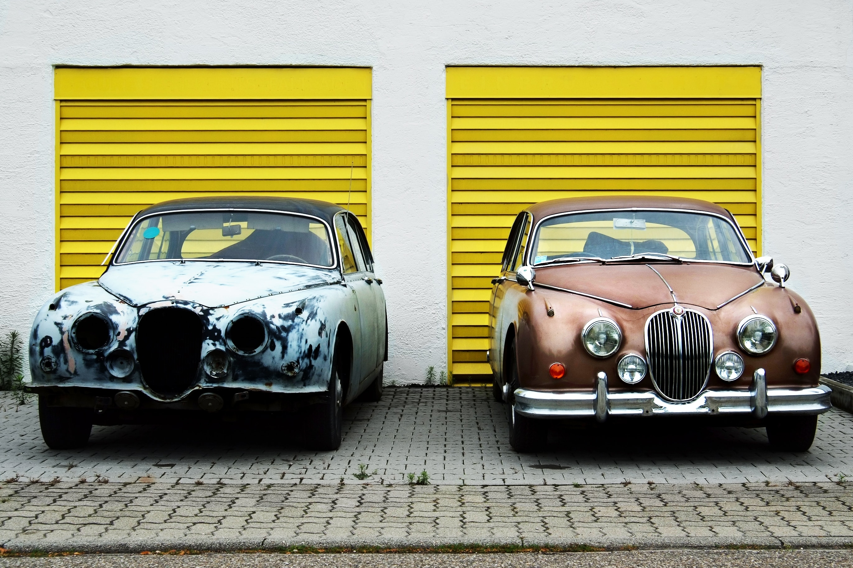 Jaguar cars in front of yellow garage door